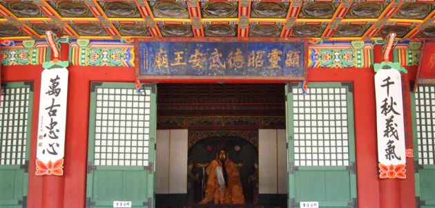 External view of the Dongmyo Shrine in Seoul, showing green doors, with red pillars and multicolored ornate ceiling and eaves.