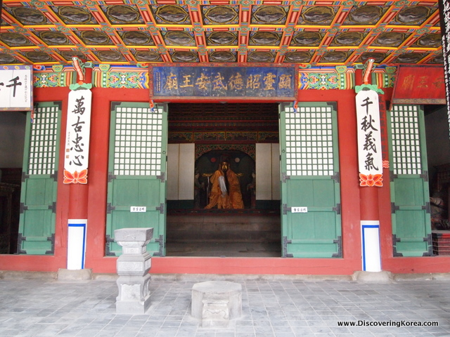 Exterior view of Dongmyo shrine, with green doors, red pillars, multicolored ceiling and eaves detail, and a stone courtyard outside.