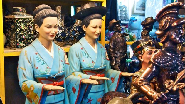 A close up of two Korean statues, ladies with their hair in a bun, wearing blue kimonos, embroidered with red flowers and green leaves, standing with their hands out, palms facing upward. Behind are various statues and vases at the Seoul Folk Flea Market.