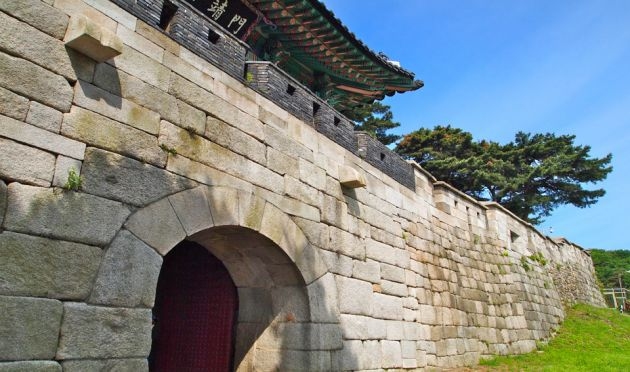 Stone block wall with an arched doorway, at Seoul fortress, a roof visible in the background, and trees and blue sky behind.