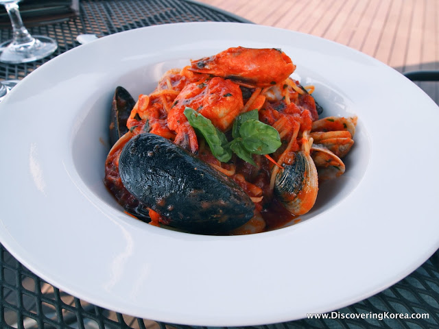 A white bowl with seafood pasta, mussels and shrimp, on a metal table.