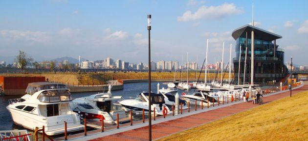 A line of boats moored at Seoul Marina, with a red brick walkway and grass on the river shores. In the background is the large glass marina building and soft focus cityscape against a blue sky.
