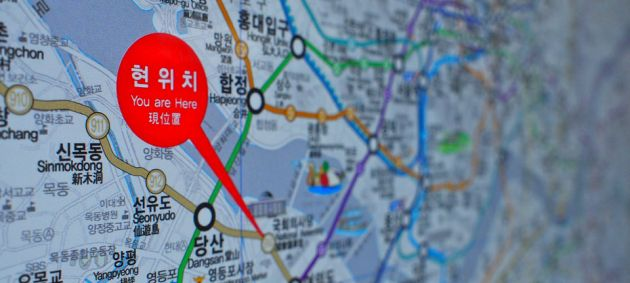 Close up of a city map showing a metro line, and a red pointer with white text. The background fades to soft focus.