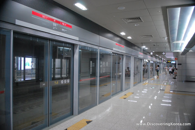 Inside Seoul's metro station, showing polished stone floors, with yellow markers at the glass doors to the left of the frame in front of the train tracks.