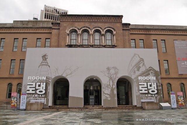 External view of the Seoul Museum of Art, a large stone building with arched windows in the center of the frame, and an external structure at the entranceway.