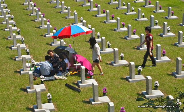 Light colored grave stones on green grass at Seoul National Cemetary. In the middle of the frame are a group of people sitting on the ground near one of the graves, with a blue, red and white umbrella.