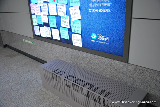 A gray metal bench with ventilation holes and the words 'Hi Seoul' in black lettering. To the top of the frame is a blue sign with post it notes in Korean.