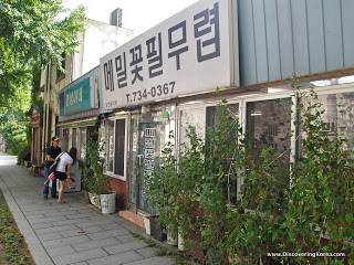 View of shopfronts of noodle bars in Seoul. to the right of the frame is glass doors with trees outside, to the left is the sidewalk and two people looking through a window.