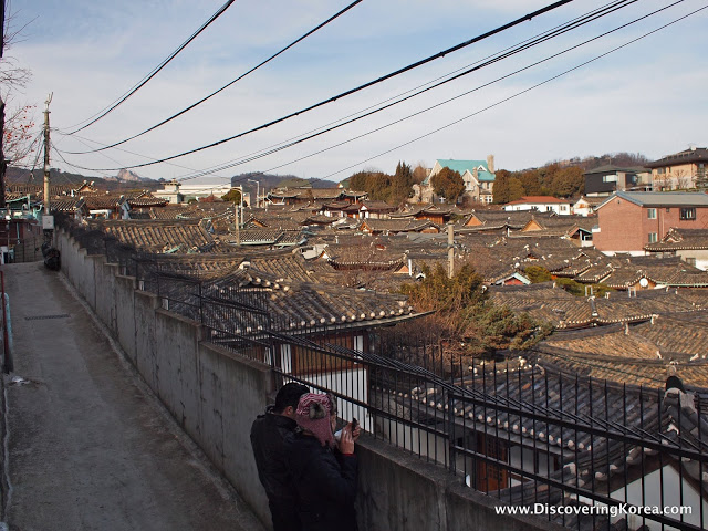 Two people looking through metal grilles across the rooftops of Bukchon Hanok village. Electricity wires run overhead.