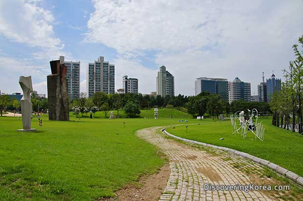 Seoul's Olympic Park, a brick walkway with lawns on either side, large geometric sculptures to the left of the frame, and tall buildings in the background, with a blue, cloudy sky.