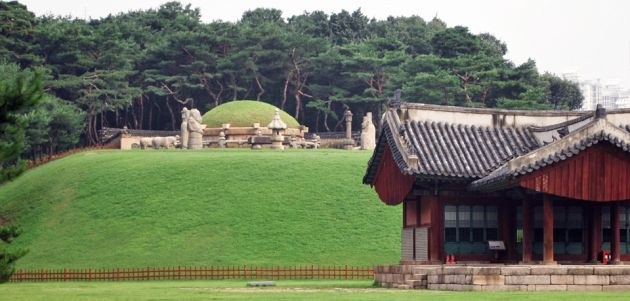 The entrance to Seoul Royal Tombs, with a wooden building to the right of the frame, with a traditional curved roof, to the center of the frame is a large round mound of grass surrounded by a stone wall, in the foreground are neat lawns and in the background a pine forest.