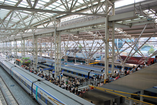 Looking down on trains at Seoul station, large groups of pedestrians on the platforms, white metal roof structure with a glass ceiling.
