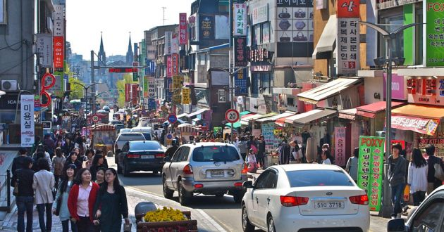 A busy street in Edae, Seoul, with pedestrians on the sidewalks and cars on the road. Variously colored shops flanking the road, with signs in Korean lettering.