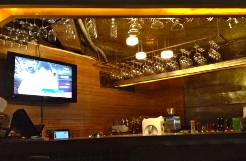 A bar, with a television on the wall, glasses hanging from shelves above, dimly lit.