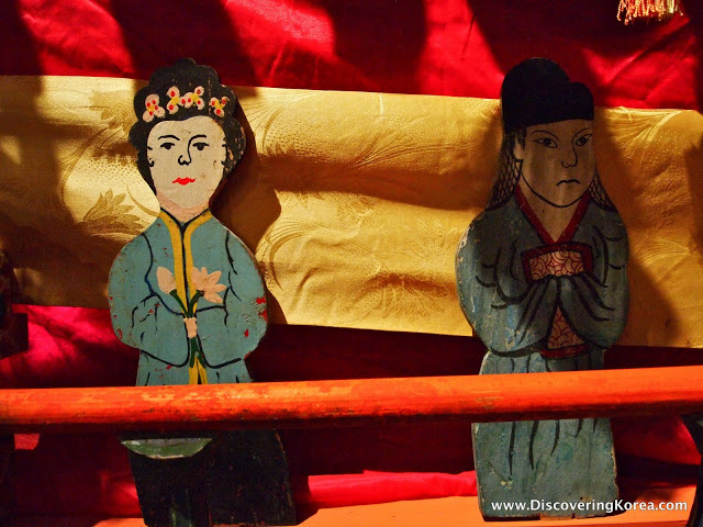 Two wooden figurines, one smiling, one frowning, in front of a background of red and yellow rolls of fabric.