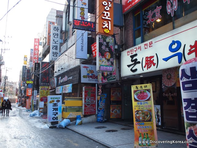 A street in Sinchon, colorful shop fronts with menus, and banners on the street, and two pedestrians in the background.