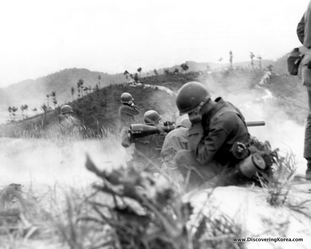 Black and white image of soldiers on the battlefields in Korea. To the front are four soldiers with guns, aiming over the mountains in the background.