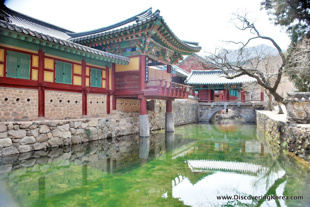A moat surrounds the Songgwangsa temple, to the left of the frame is a brightly painted building, with a balcony jutting out over the moat, in the center is a stone bridge and the water reflects the buildings and trees.