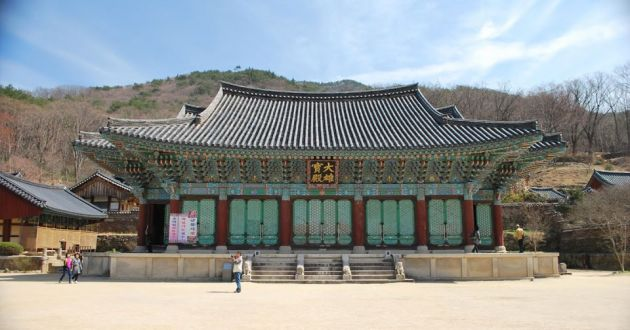 Looking across a stone courtyard at the ornate Songgwangsa temple, with turquoise shutters on the windows, ornate painted wood carving under the roof eaves and the traditional curved roof. Korean lettering in gold above the entrance door.