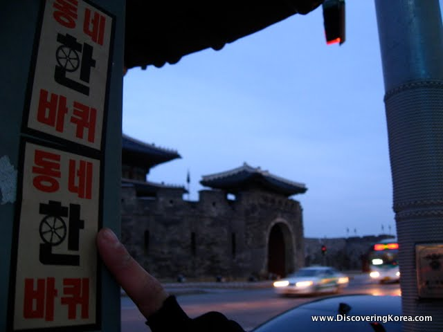 A finger points at sticker on a lamp post, with soft focus buildings and cars in the background, at dusk.