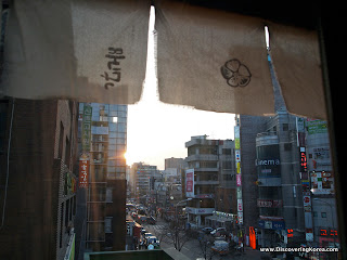 Street scene with fabric hanging from the top of the frame, looking out onto evening sunshine with buildings, cars and pedestrians.