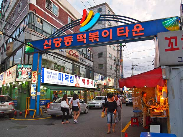A street in Seoul, with a blue and red sign over the street, in the background are lots of shopfronts and restaurants and people walking around.