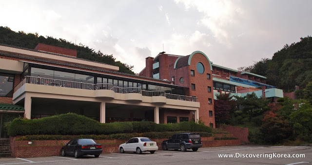 Suanbo Park hotel from the outside. A red brick building with a light stone balcony. Three cars parked below with vegetation to the right.