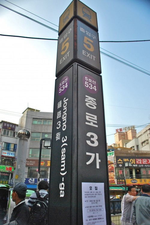 A subway sign in Seoul, a black pillar with Korean writing and buildings and pedestrians behind, with a blue sky.