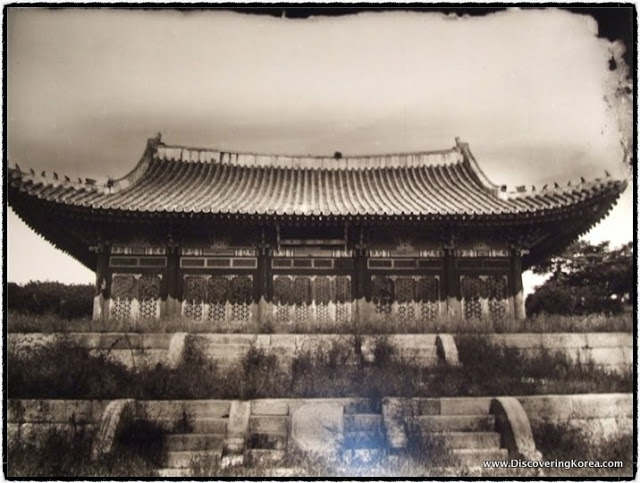 Historical sepia image of the view up the steps towards the Gyeonghuigung summer palace. An ornate roof covers a wooden building with stone steps.