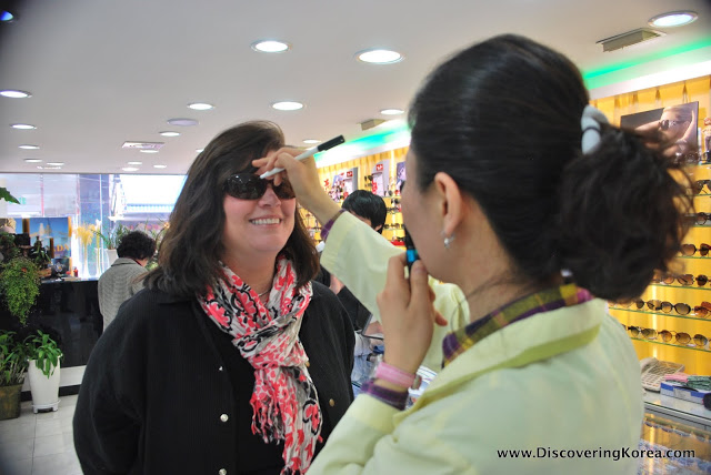 A woman with a red and black scarf is being measured for sunglasses by a sales assistant at Namdaemun market. The sales assistant is dressed in a light green coat, and the background shows rows of sunglasses on display racks.