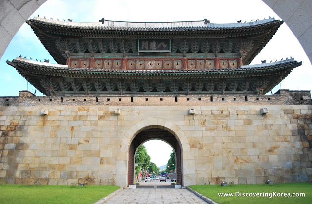 Light stone arched entrance way to Suwon fortress with ornate roof.