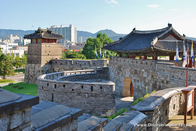 Hwaseong Fortress showing a semicircle battlement and ornate roof, with flags to the right of the frame.