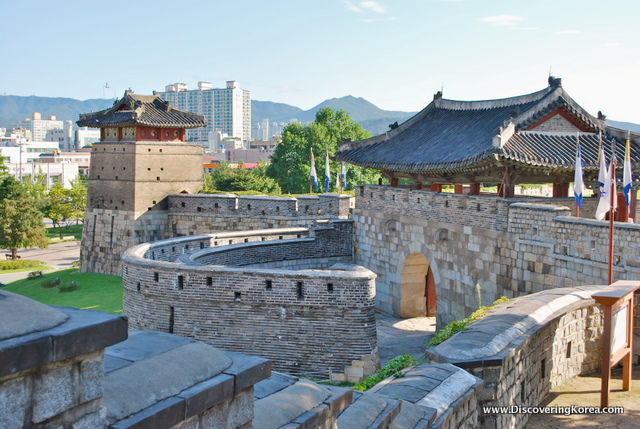 Light stone colored semicircle walls of the Suwong Hwaseong fortress, with ornate roofs.