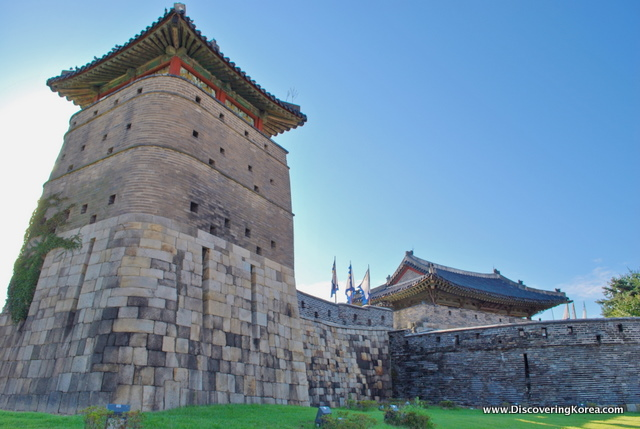 Suwon Hwaseong fortress seen in sunlight, view up to one of the stone battlements, with ornate roof.