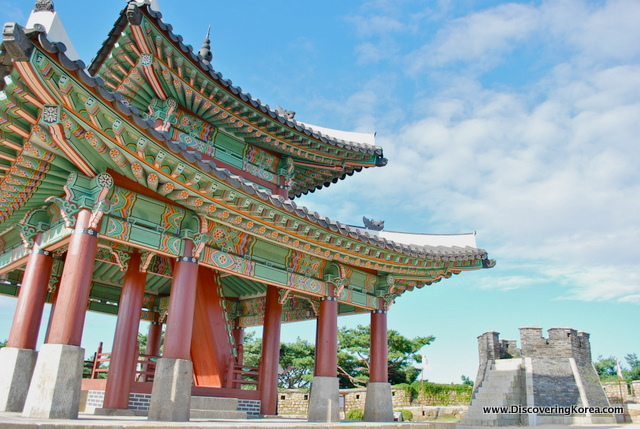 Looking up at the green, orange, and red ornate roof of Suwon Hwaseong fortress.