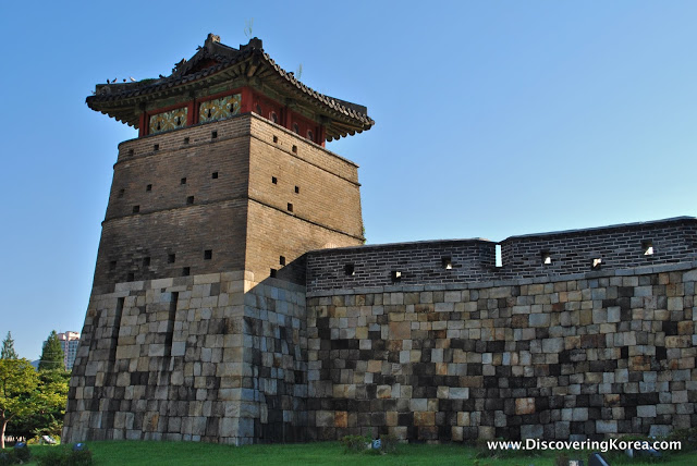 Suwon fortress walls in light and dark stone, with red ornate roof, blue sky and sunshine.
