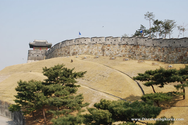 Battlement walls of Suwon fortress, light stone, with trees in the foreground.