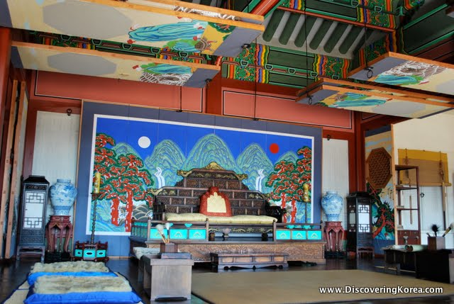 Ornate, multicolored chamber in Suwon Hwaseong fortress. Painted mural on the walls and ceiling. Large wooden furniture and ceramic vases.