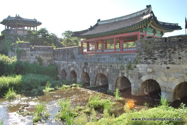 Stream running through stone arches underneath part of the wall of Suwon Hwaseong fortress, with an ornate roof.