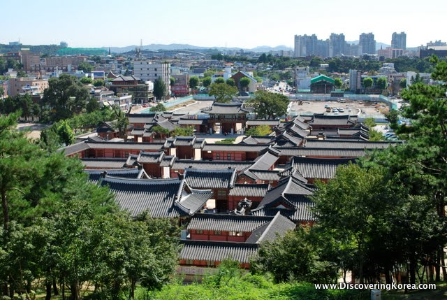 View over rooftops of the town from Suwon Hwaseng fortress. Red brick houses and dark rooftops in the foreground, city view in soft focus behind.