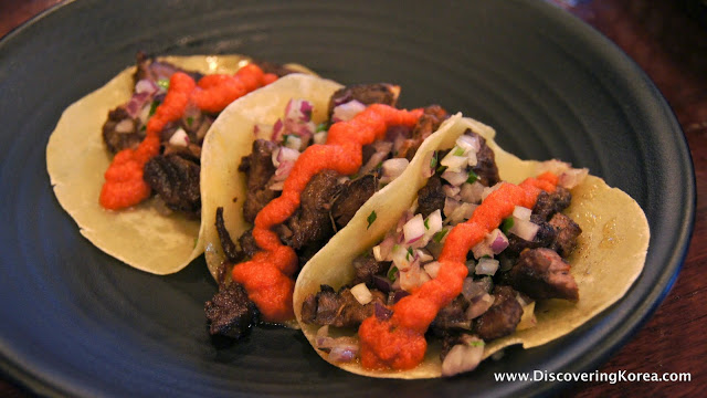 Three soft tacos with meat, salsa and a red sauce filling, on a black plate in Seoul.