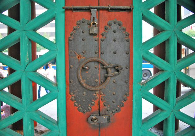 Close up of an ornate door, with turquoise carving on either side of red wood with slightly rusty metal locks and latches.