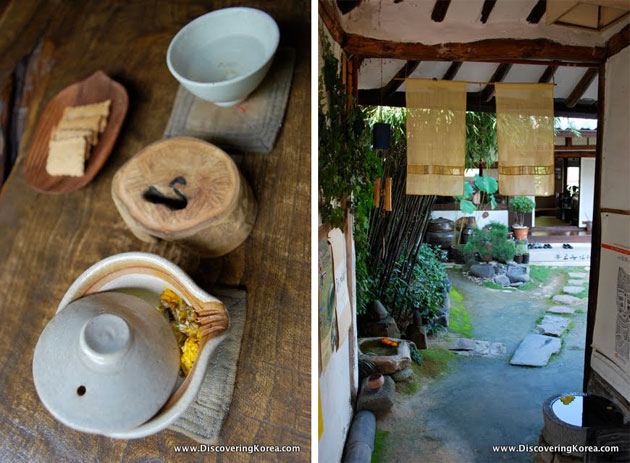 A tea house in Jeonju. On the left is a pot of tea on a wooden surface, on the right is a view into a courtyard with paving stones.