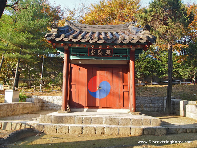 Red wooden building set on a stone platform with trees in the background at Cheonggyesan, showing fall colors in sunshine.