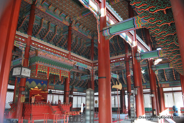 A red and multicolored ornate throne room at Gyeongbokgung. Pictured are ornate pillars and intricate fret work on the ceiling, with steps up to a throne to the left of the frame.
