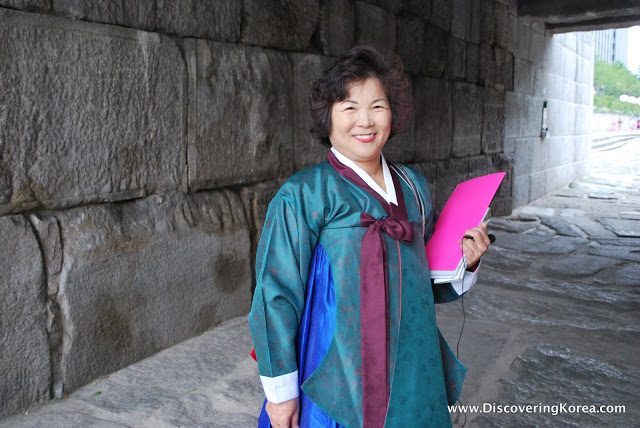 A smiling tour guide under a bridge at Cheonggyecheon stream, wearing a blue tunic, and carrying a pink folder.