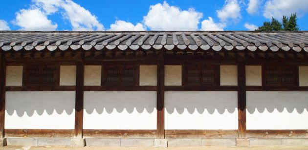 Unhyeongung Royal Villa seen from the exterior with stone steps leading up to a white building with wooden posts and window frames. A dark roof, with a blue sky and clouds in sunshine.