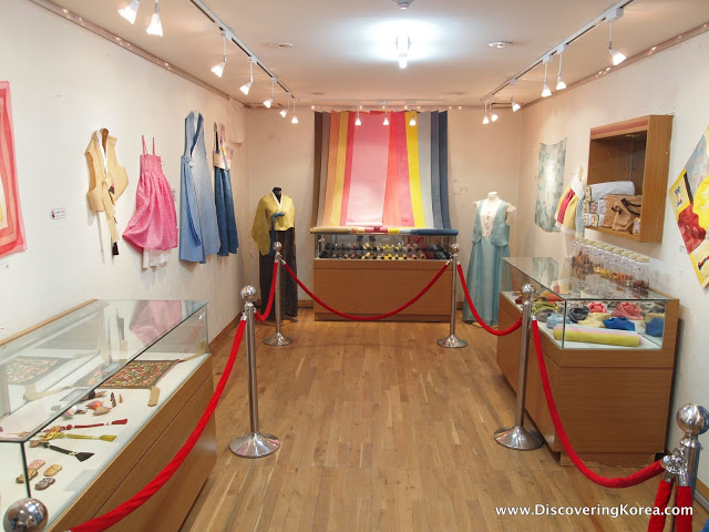Exhibition at Unhyeongung royal villa, with glass cabinets containing exhibits, with two mannequins behind and draped fabric.