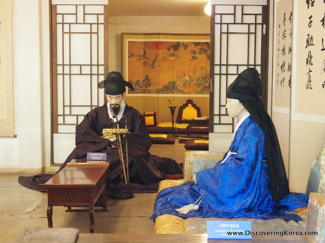 Interior Unhyeongung royal villa with statues of two people sitting, one wearing black robes and a hat, and the woman wearing blue robes. Looking behind, an illustrated screen.