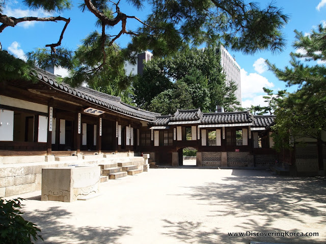 A stone courtyard with Unhyeongung royal villa in the background with white walls and wooden frame. Blue sky with clouds and sunshine, with trees.